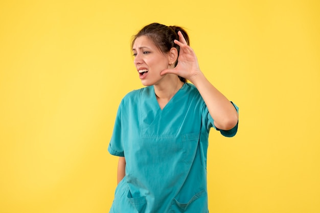 Front view female doctor in medical shirt listening on yellow background
