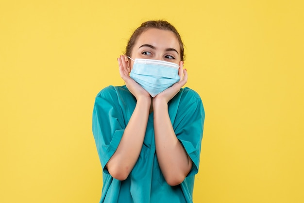 Front view female doctor in medical shirt and mask, health uniform virus covid-19 pandemic color