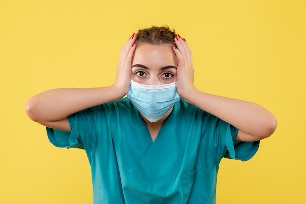 Medico femminile di vista frontale in camicia e maschera mediche, uniforme di colore pandemico covid-19 del virus della salute