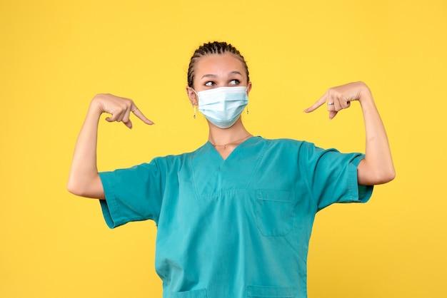 Medico femminile di vista frontale in camicia e maschera mediche, virus dell'infermiera dell'ospedale di salute pandemica covid-19