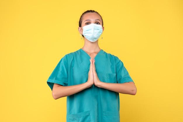 Medico femminile di vista frontale in camicia medica e maschera che prega, ospedale covid-19 del virus dell'infermiera di salute del medico pandemico