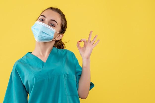 Medico femminile di vista frontale in camicia e maschera mediche, pandemia covid-19 di colore di salute del virus