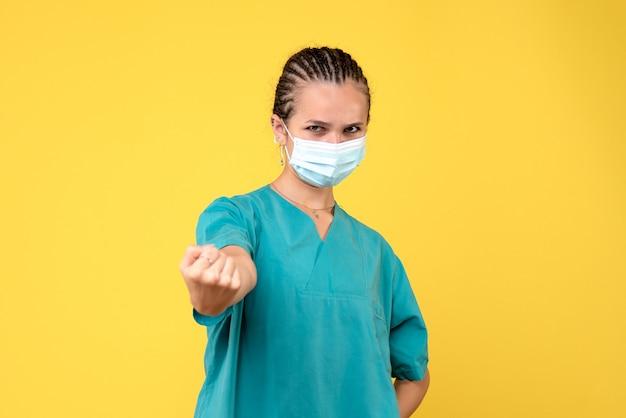 Medico femminile di vista frontale in camicia e maschera mediche, colore pandemico covid-19 dell'ospedale dell'infermiera di salute del virus