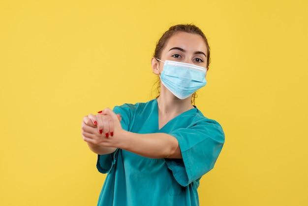 Medico femminile di vista frontale in camicia medica e maschera, salute uniforme covid-19 pandemia di virus