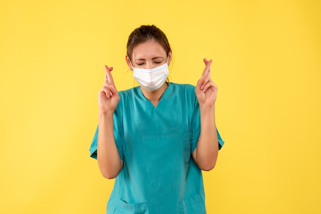 Vista frontale medico femminile in camicia medica e maschera con le dita incrociate sulla scrivania gialla ospedale pandemia colore covid- salute virus medic