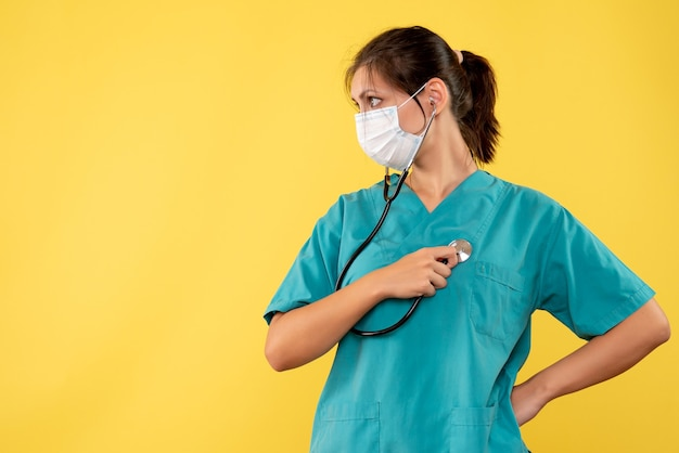 Front view female doctor in medical shirt and mask with stethoscope on a yellow background