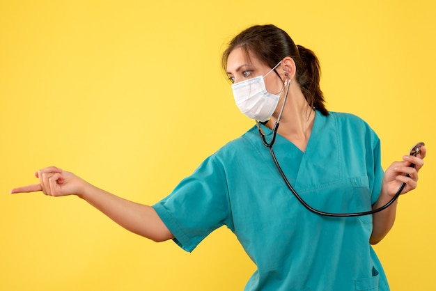 Front view female doctor in medical shirt and mask with stethoscope on yellow background
