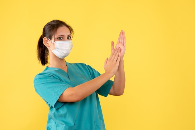 Front view female doctor in medical shirt and mask on a yellow background