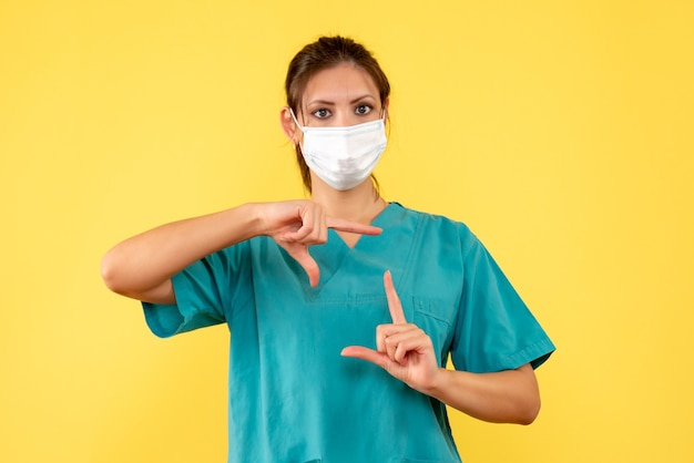 Front view female doctor in medical shirt and mask on the yellow background