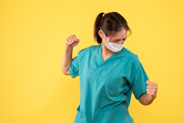 Front view female doctor in medical shirt and mask on yellow background