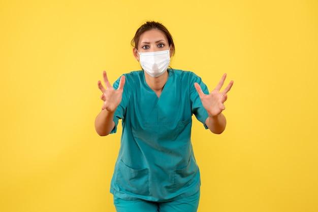 Medico femminile vista frontale in camicia medica e maschera su sfondo giallo