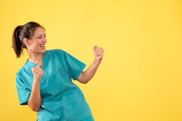 Medico femminile vista frontale in camicia medica che si rallegra su sfondo giallo