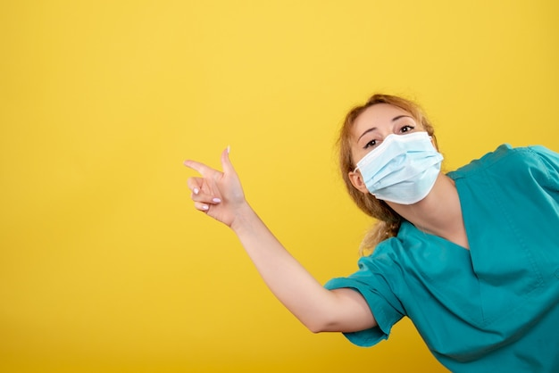 Front view female doctor in medical shirt and sterile mask, hospital color covid-19 health emotion pandemic