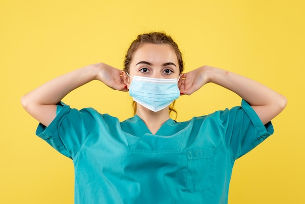 Front view female doctor in medical shirt and sterile mask, virus uniform color covid-19 health emotion