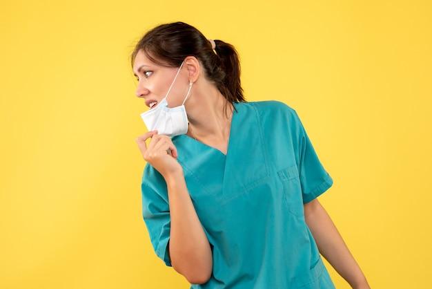 Medico femminile di vista frontale in camicia medica e maschera sterile su fondo giallo