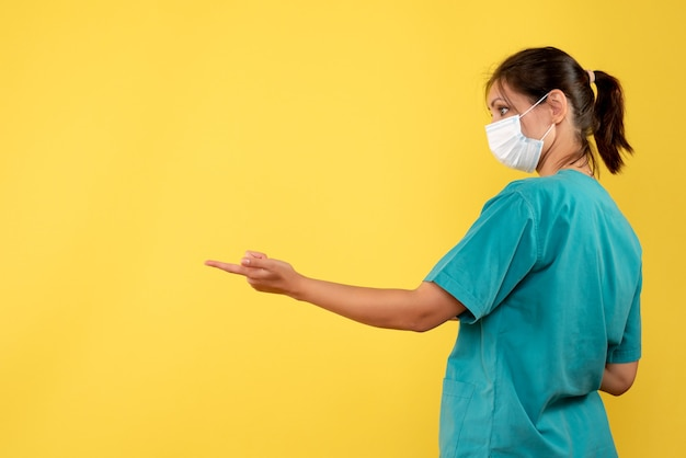 Front view female doctor in medical shirt and sterile mask on yellow background