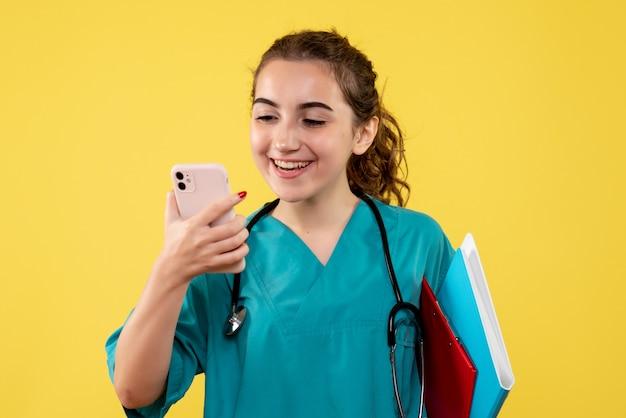 Medico femminile di vista frontale in camicia medica con note e telefono, virus covid-19 di salute pandemia uniforme di emozione