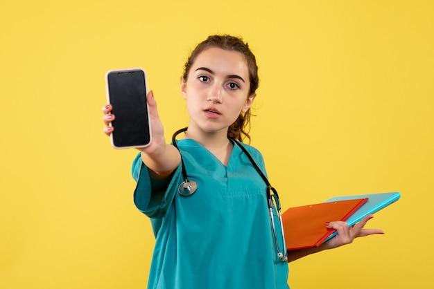 Medico femminile di vista frontale in camicia medica con note e telefono, virus covid-19 pandemico uniforme di emozione di salute