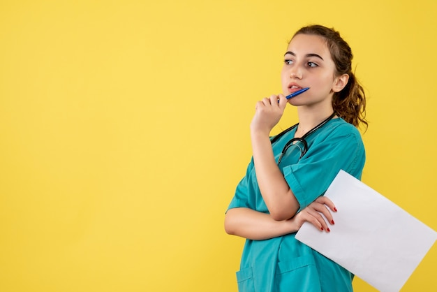 Front view female doctor in medical shirt with papers and stethoscope, uniform pandemic health covid-19 emotion virus