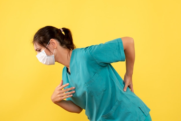 Front view female doctor in medical shirt with sterile mask having back ache on a yellow background