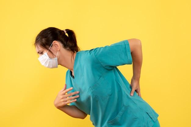 Medico femminile di vista frontale in camicia medica con maschera sterile che ha mal di schiena su uno sfondo giallo