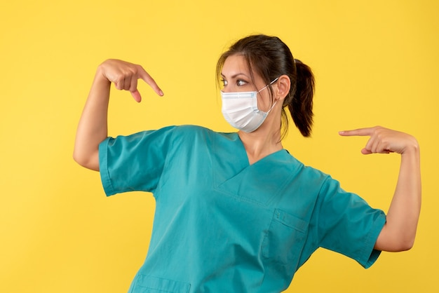 Front view female doctor in medical shirt with sterile mask pointing at herself on yellow background
