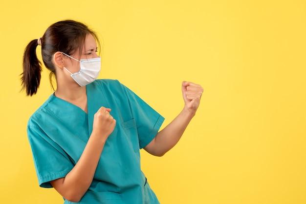 Medico femminile vista frontale in camicia medica e con maschera sterile su sfondo giallo