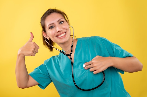 Front view female doctor in medical shirt with stethoscope on yellow background