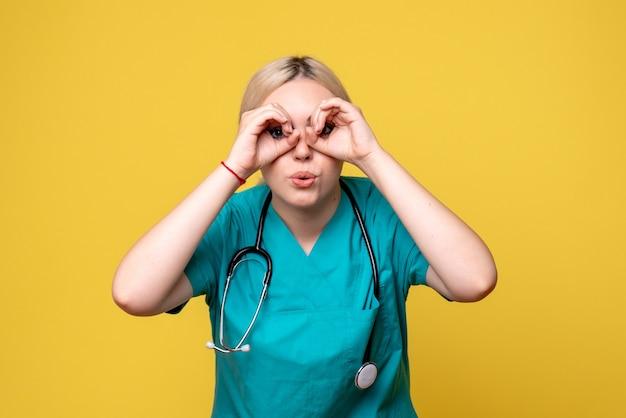 Vista frontale della dottoressa in camicia medica con lo stetoscopio sulla parete gialla