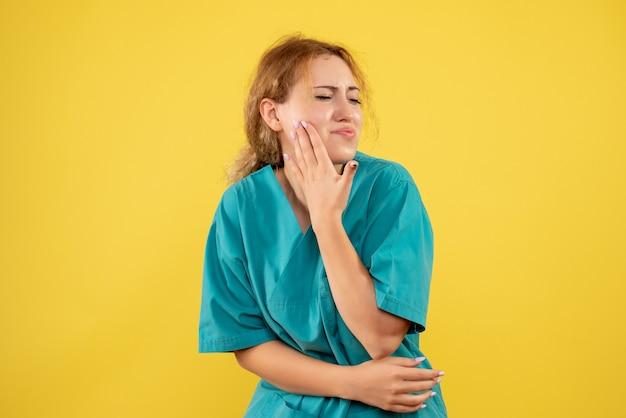 Vista frontale della dottoressa in camicia medica con mal di denti sulla parete gialla