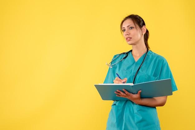 Medico femminile di vista frontale in camicia medica che scrive le note su fondo giallo