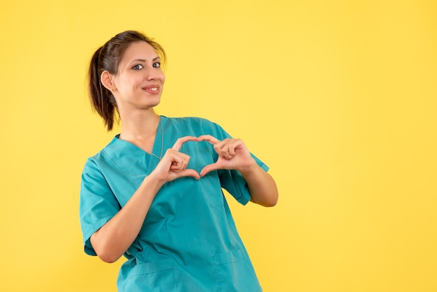 Front view female doctor in medical shirt on a yellow background
