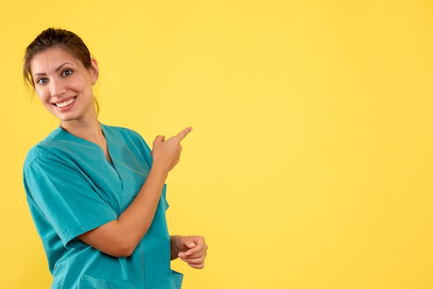 Front view female doctor in medical shirt on the yellow background