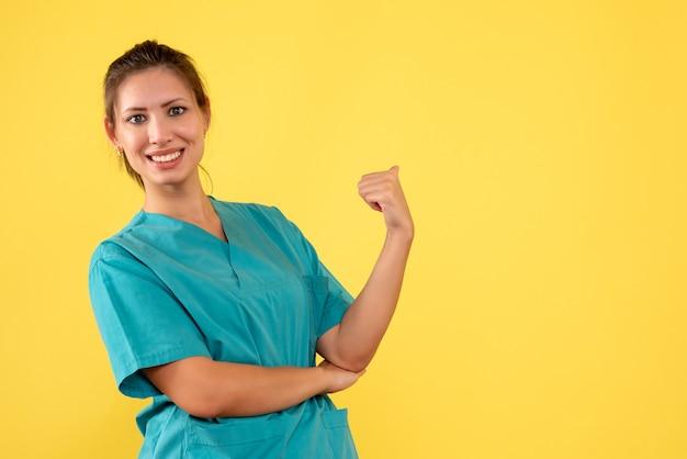 Medico femminile di vista frontale in camicia medica su una priorità bassa gialla