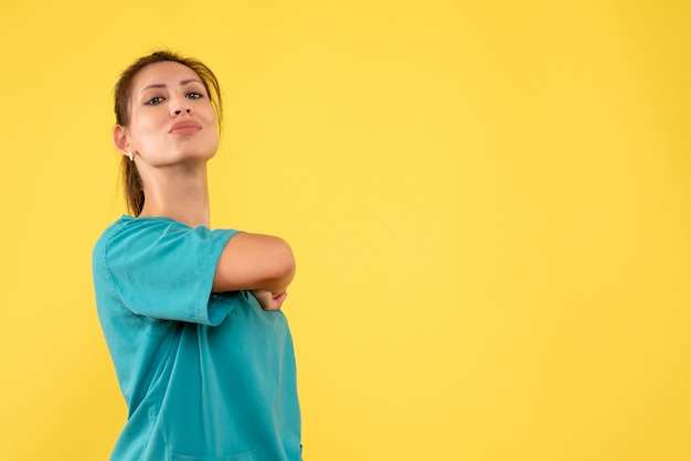 Front view female doctor in medical shirt on yellow background