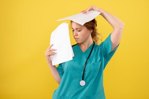 Vista frontale del medico femminile in tuta medica che tiene analisi sulla parete gialla