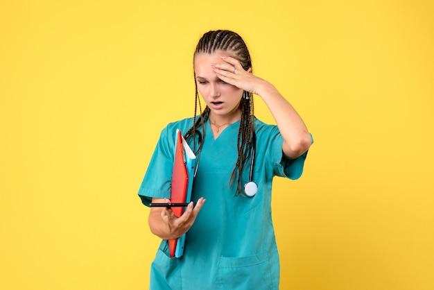 Vista frontale della dottoressa in tuta medica tenendo il telefono e le note sulla parete gialla