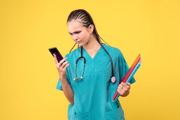 Vista frontale della dottoressa in tuta medica tenendo il telefono sulla parete gialla