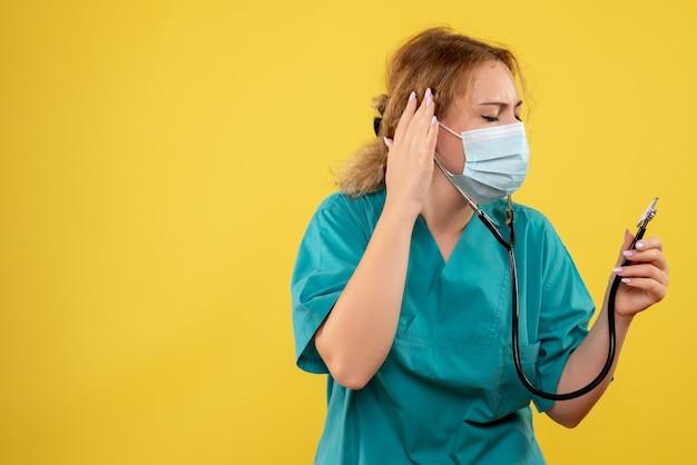 Vista frontale della dottoressa in tuta medica e maschera con lo stetoscopio sulla parete gialla