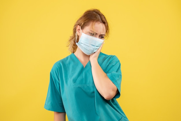 Front view of female doctor in medical suit and mask on the yellow wall Free Photo