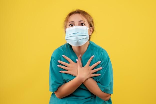 Vista frontale della dottoressa in tuta medica e maschera sulla parete gialla
