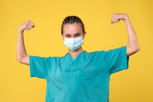 Vista frontale della dottoressa in tuta medica e maschera sterile che flette sulla parete gialla