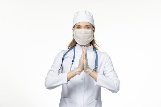 Vista frontale dottoressa in tuta medica che indossa una maschera a causa del coronavirus sulla malattia da scrivania bianca chiara covid - malattia da virus pandemico