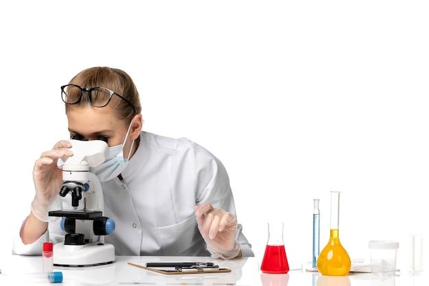 Medico femminile di vista frontale in vestito medico che indossa la maschera a causa di covid utilizzando il microscopio su uno spazio bianco chiaro