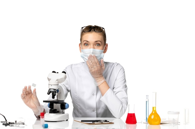 Medico femminile di vista frontale in vestito medico che indossa la maschera a causa del lavoro covid sullo spazio bianco