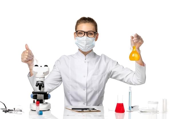 Medico femminile vista frontale in tuta medica che indossa la maschera a causa di covid lavorando con soluzioni su uno spazio bianco
