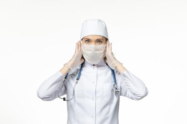 Medico femminile di vista frontale in vestito medico che indossa maschera e guanti a causa del coronavirus sulla malattia da virus della malattia pandemica covid della parete leggera