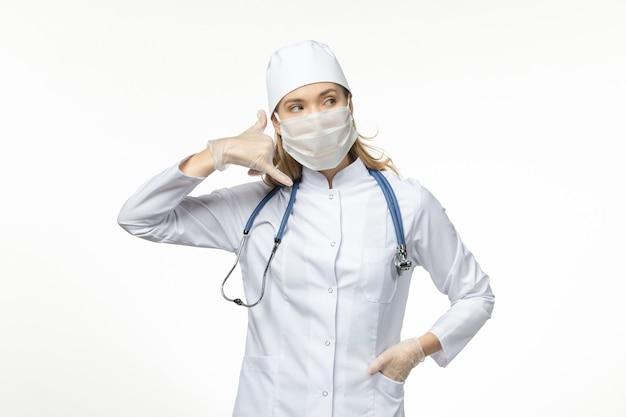 Medico femminile di vista frontale in vestito medico che indossa maschera e guanti a causa della telefonata del coronavirus posa sul virus della malattia pandemica covid della scrivania bianca