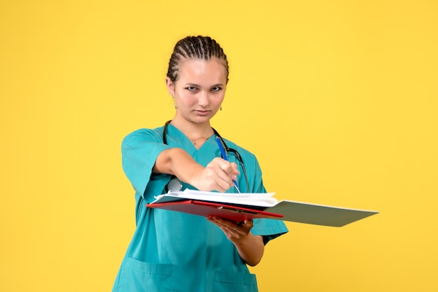 Front view of female doctor in medical suit with different analysis on yellow wall