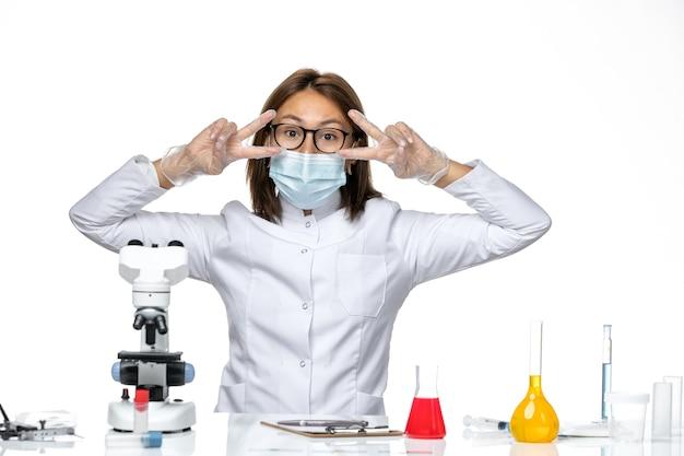 Medico femminile vista frontale in tuta medica con maschera a causa di covid in posa su uno spazio bianco chiaro
